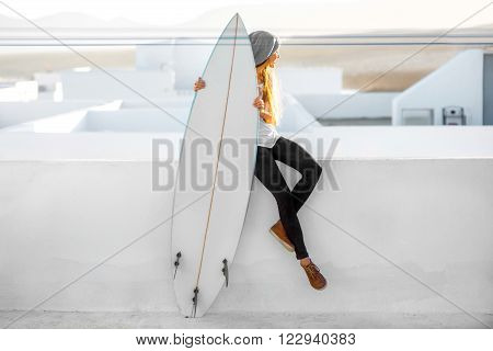 Young smiling woman in white t-shirt and hat sitting with surfboard on the roof top on the white city background in the morning