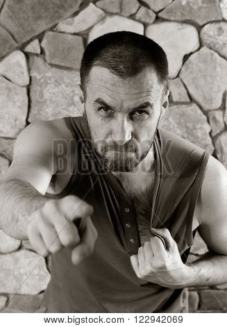 aggressive unshaven white man points his finger and tears on his shirt. black and white photo