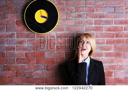 Young attractive woman under the clock, on brick wall background