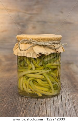 pickled garlic sprouts in glass jar closeup. home canning