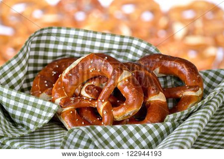 Fresh handmade original Bavarian pretzels from the domestic master baker on a green checkered tea towel; many blurry pretzels in the background