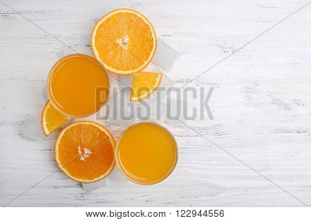 Two orange juices with cubes of ice and orange on white wooden table background, closeup