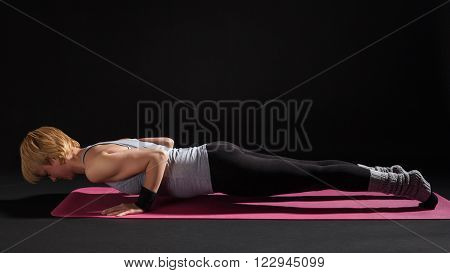 Young woman practicing yoga, Chaturanga Dandasana / Four-Limbed Staff Pose