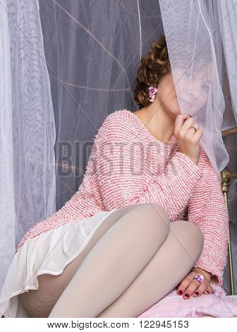 Portrait of hiding in tulle curtain beautiful woman sitting in bed with canopy and looking at camera