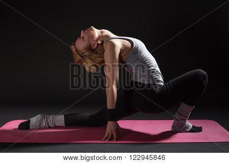 Young woman practicing yoga, Virabhadrasana / variation of Warrior pose