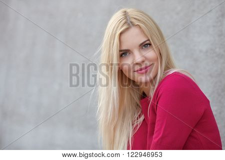 Close up portrait of young beautiful blonde woman with trendy bright makeup in fuchsia blouse against concrete wall blurred background