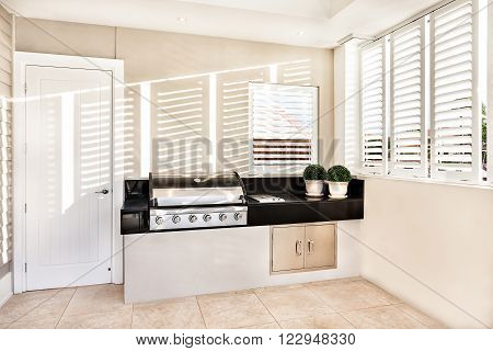 Electrical automatic cooking gas in kitchen with two flower pot kept on slab and window open with sunlight falling inside of a luxury house