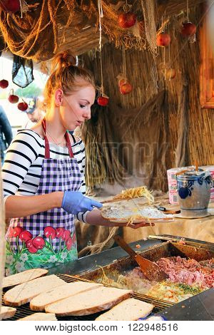 GDANSK, POLAND - JULY 29, 2015: Young woman makes traditional sandwich with lard spread onions sausage and cucumbers on the summer fair in downtown Gdansk
