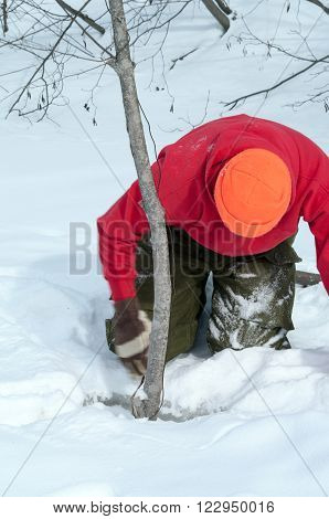 Trapper clearing ice and snow from water trap in the winter