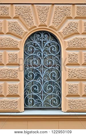 Window with arch and decorative lattice on a background of beige wall. From the series window of Saint-Petersburg.