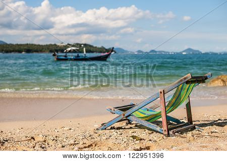 Deckchairs on a beautiful sandy beach with colorful nature on background. Vacation concept.
