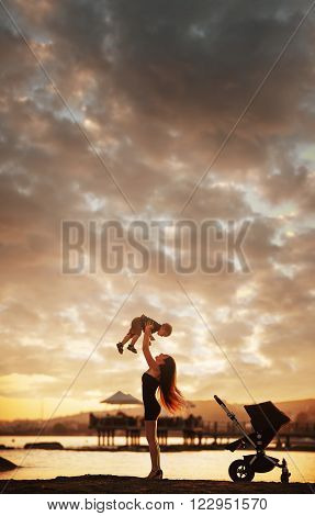 Young attractive mother and her baby boy having fun at sunset on the beach. ** Note: Visible grain at 100%, best at smaller sizes