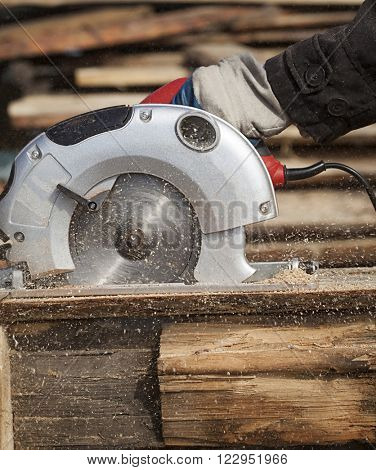 a man works outdoors with a circular saw