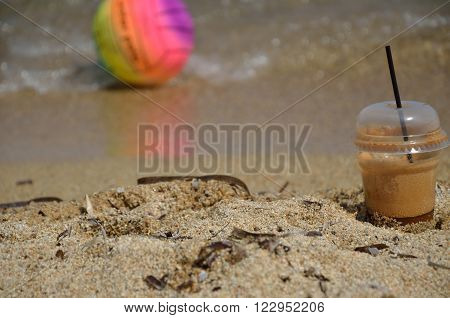 Coffee frappe on sea shore with colorful beach ball in background