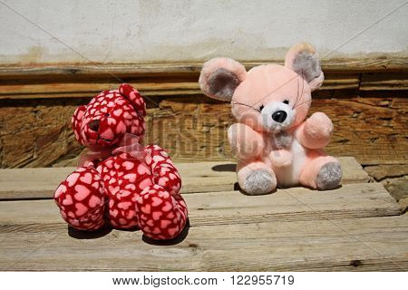 Adorable colorful stuffed fluffy toys on a bench