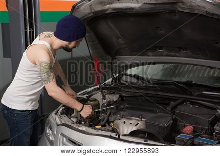 Motor mechanic diagnosing automobile car engine before maintenance at repair service station. Handsome man solving problem with engine or motor.