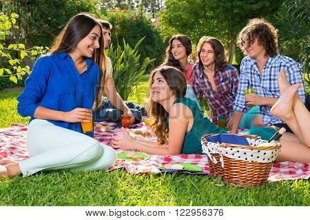 Six friends relaxing on sunny afternoon. Six happy friends relaxing on a sunny afternoon in the park sharing food and drinks on a sunny afternoon in the park.