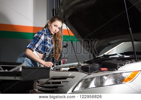 Sexy girl repairing automobile or car at repair shop. Long-haired lady is professional mechanic. Repairwoman looking at camera.