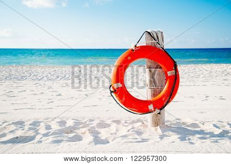 Life buoy on a pole on a sandy beach with blue ocean water