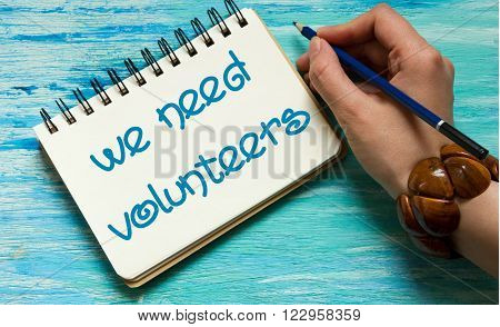 we need volunteers quotes word conceptual labels for postcards business ideas announcements write a note with beautiful handwriting of a female hand with text on wooden background