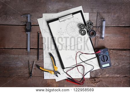 Digital multimeter and blueprints on a wooden background.