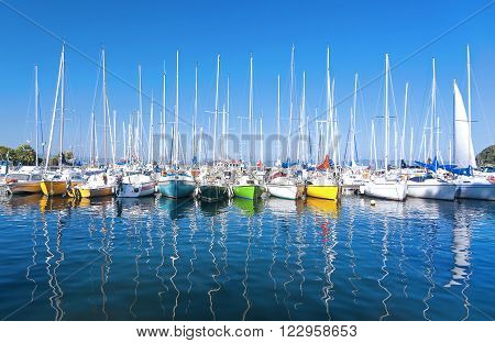 Series of small colored sailboats parked on the dock of a lake. reflection on the water.