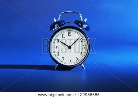 Alarm clock on a blue background.