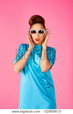 portrait on young beautiful woman in blue silk dress and white sunglasses ot the pink background ** Note: Soft Focus at 100%, best at smaller sizes