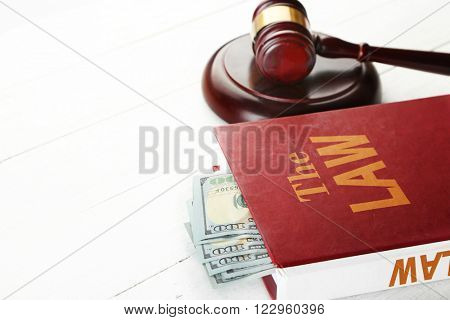 Gavel with book and money on wooden table closeup