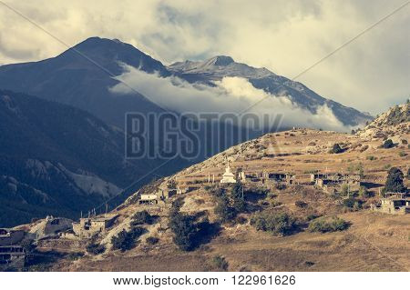 Buddhist religious buildings build on a grassy slope. Annapurna region in Nepal.