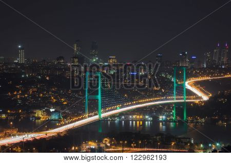 Turkey Istanbul glowing hanging bridge over the Bosphorus on the background panorama of the city at night.