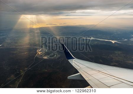 Nice view from the airplane the rays of the sun breaking through the clouds you can see an airplane wing a beautiful landscape