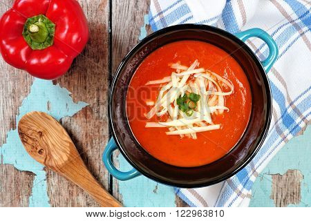 Red Pepper Soup Topped With Shredded Cheese And Green Onions, Overhead Scene On Rustic Blue Wood Bac