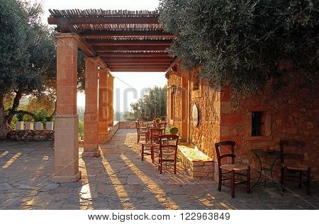 Rural greek country outdoor restaurant on pergola terrace with empty table, Crete, Greece. Sunset light