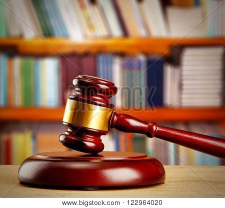 Judge gavel on wooden table on book shelves background
