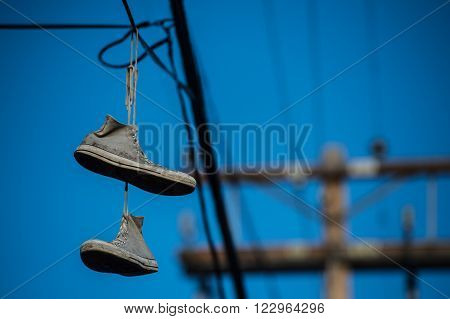 high top sneakers hanging by laces on telephone wire