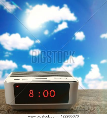 Digital clock showing 8:00 o'clock on wooden table,  blue sky background