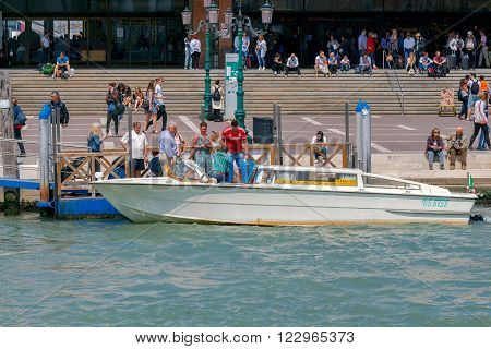 Venice, Italy - May 24, 2015: The main railway station and the pier for vaporetto in Venice. Water Taxi is transporting tourists to the city from the main station.