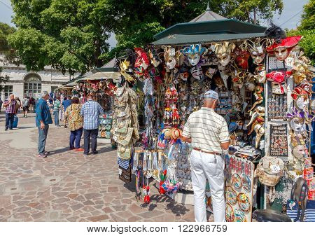 Venice, Italy - 25 May, 2015: Sale of traditional souvenirs and gifts, such as masks, magnets, clothing, guidebooks for tourists visiting Venice. This activity brings good profit to sellers.