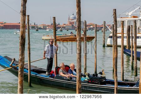 Venice, Italy - 25 May, 2015:  Two elderly women of retirement age are floating in a gondola on the Grand Canal in Venice. A gondola ride favorite amusement of tourists in Venice.