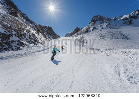 Snowboarders and off the mountain on a sunny day. Austrian Alps