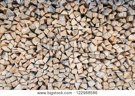 Big pile of birch wood logs stored for winter as background pattern