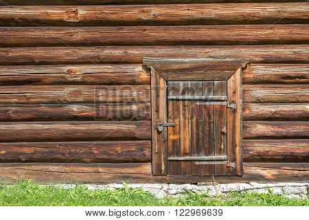 Old log house wood wall with closed door and padlock on it symbolizing secured storage or house.