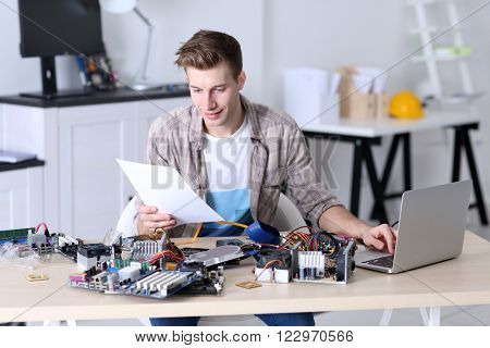 Young man repairing computer hardware and using laptop in service center