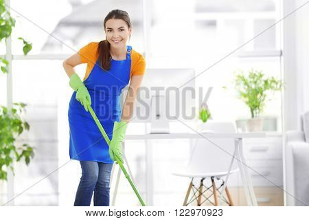 Woman cleaning with mop indoors