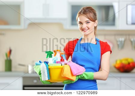 Cleaning concept. Young woman holds basin with washing fluids and rags in hands