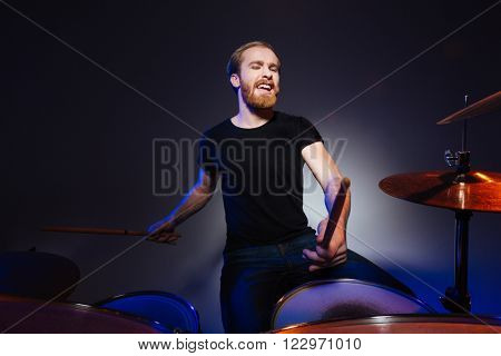Attractive bearded man drummer playing drums with passion over dark background