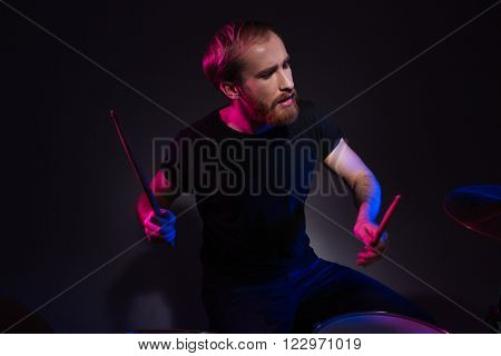Handsome young bearded man drummer sitting and playing drums with drumsticks over dark background