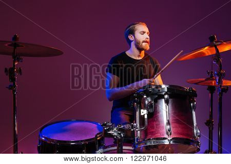 Handsome man drummer sitting and playing on his kit over dark background