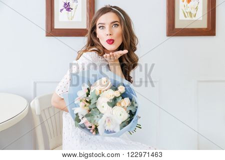 Cute lovely young woman holding bouquet of flowers and sending a kiss